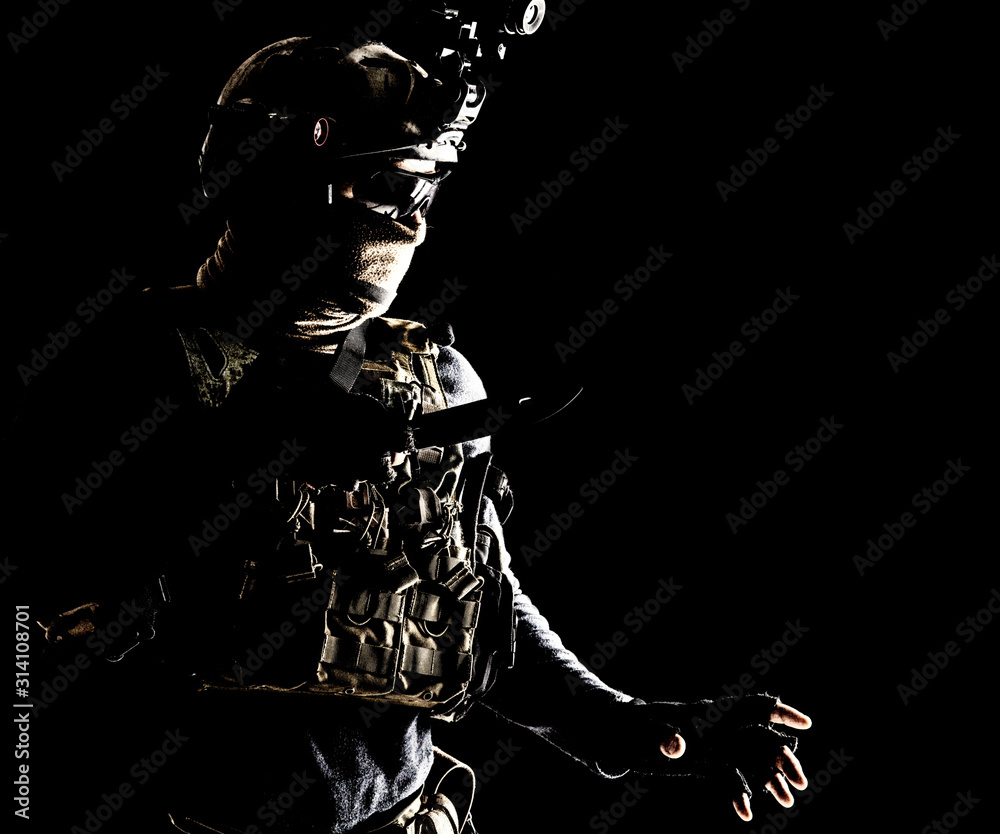 Fototapeta Special operations soldier, commando fighter, modern warfare combatant in combat uniform, helmet with night-vision, wearing mask and glasses, sneaking in darkness for sentry quiet removal with knife