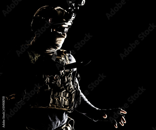 Obraz Special operations soldier, commando fighter, modern warfare combatant in combat uniform, helmet with night-vision, wearing mask and glasses, sneaking in darkness for sentry quiet removal with knife - fototapety do salonu