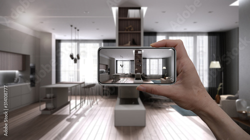Fototapeta Hand holding smart phone, AR application, simulate furniture and interior design products in real home, architect designer concept, blur background, modern kitchen and living room obraz