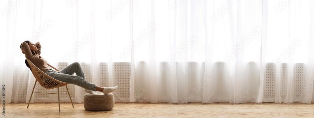 Fototapeta Young Asian Girl Relaxing In Modern Wicker Chair Near Window