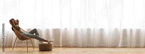 Obraz Young Asian Girl Relaxing In Modern Wicker Chair Near Window - fototapety do salonu