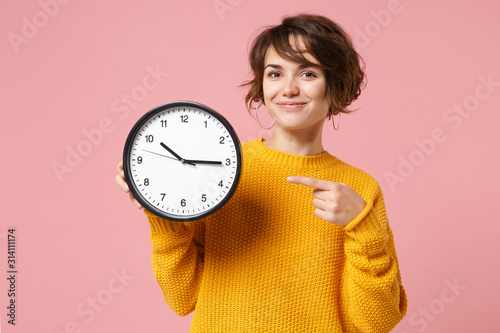 Fototapeta Smiling young brunette woman girl in yellow sweater posing isolated on pastel pink background in studio. People sincere emotions lifestyle concept. Mock up copy space. Pointing index finger on clock. obraz