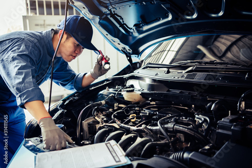 mata magnetyczna Car mechanic technician holding flashlight checking engine with checklist clipboard to maintenance vehicle by customer claim order in auto repair shop garage repair service. People occupation business
