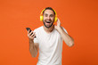 canvas print picture - Laughing young man in casual white t-shirt posing isolated on orange wall background studio portrait. People lifestyle concept. Mock up copy space. Listening music with headphones, hold mobile phone.