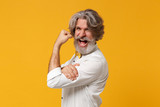 Side view of elderly gray-haired mustache bearded man in white shirt and bow tie posing isolated on yellow orange wall background. People lifestyle concept. Mock up copy space. Showing biceps muscles.