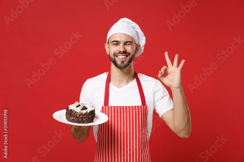 Bearded male chef cook or baker man in striped apron white t-shirt toque chefs hat posing isolated on red background Wallpaper Mural