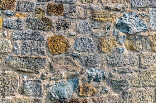 Photo  Natursteinmauer mit Steinen in mehreren Farben wie dunkelgrau, graublau, über ei