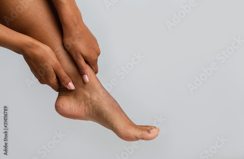 Close up of black woman massaging her ankle Canvas Print