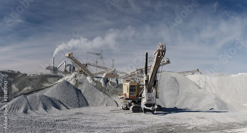 Quarry excavator in the background of hills of cruched stone next to a mining enterprise, panorama Fototapeta