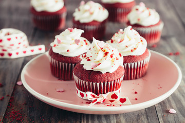 Red velvet cupcakes on a pink dish on a rustic wooden table