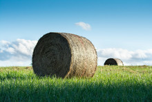 Unique View Of Two Hay Bales Taken From Low Angle And Featuring Beautiful Blue Sky, Clouds, And Green Grass