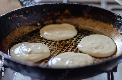 Obraz Frying fritters in a pan. Four raw pancakes in a hot pan. Raw yeast dough. Traditional cuisine. Selective focus. - fototapety do salonu