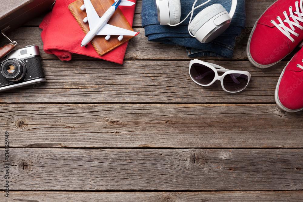 Fototapeta Suitcase, camera, clothes and travel accessories