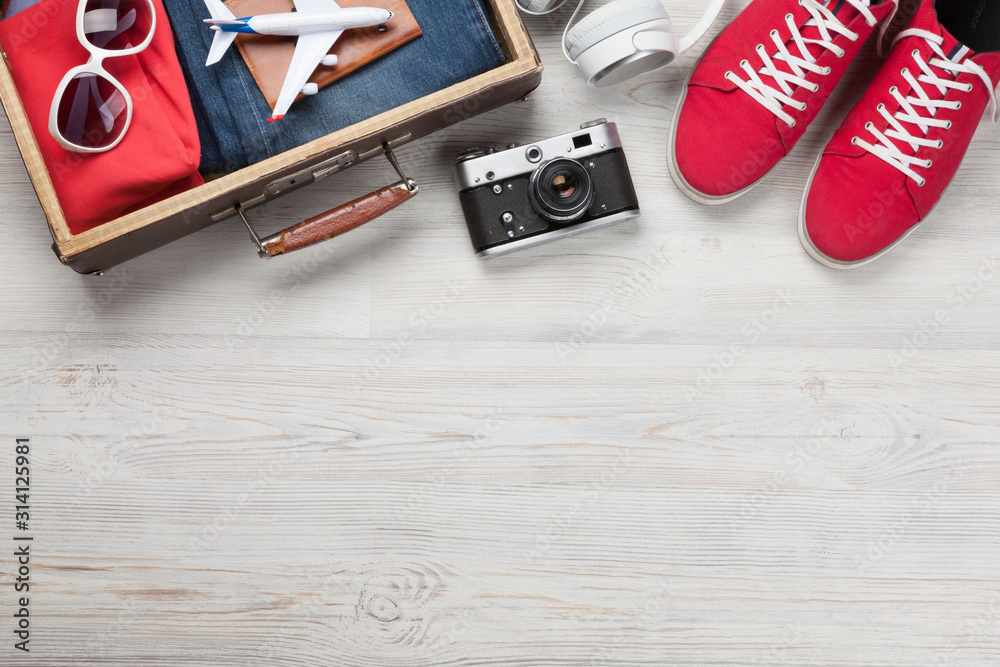 Fototapeta Suitcase with clothes and travel accessories