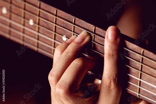Girl strumming the strings of a guitar. Fototapeta
