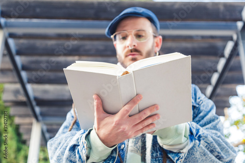 Obraz Bohemian young man reading a book. Culture concept - fototapety do salonu