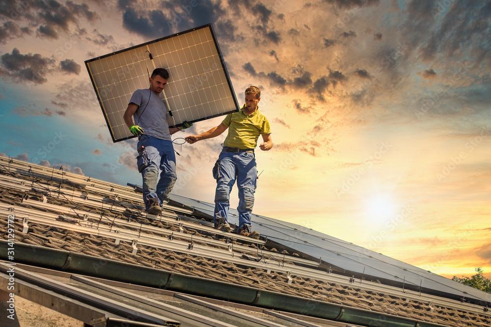 Fototapeta Installing solar photovoltaic panel system. Solar panel technician installing solar panels on roof. Alternative energy ecological concept.
