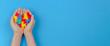 Leinwandbild Motiv Kid hand holding colorful heart on light blue background. World autism awareness day concept