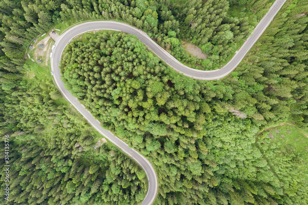 Fototapeta Top down aerial view of winding forest road in green mountain spruce woods.