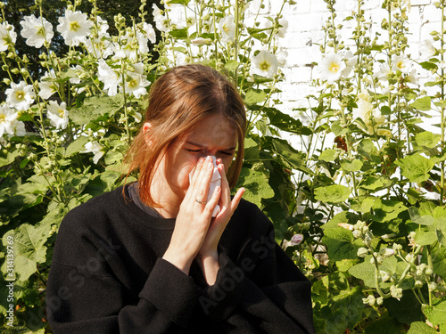 a girl with allergies sneezes into a handkerchief on the street among flowers, t Wallpaper Mural
