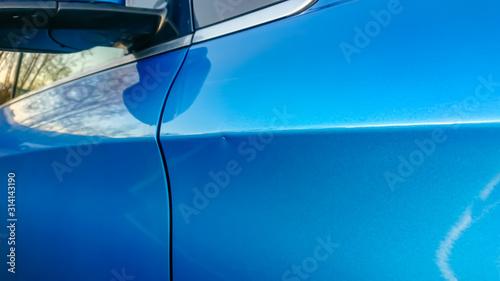 Obraz na plátně A small dent in the fender of a blue metallic European car
