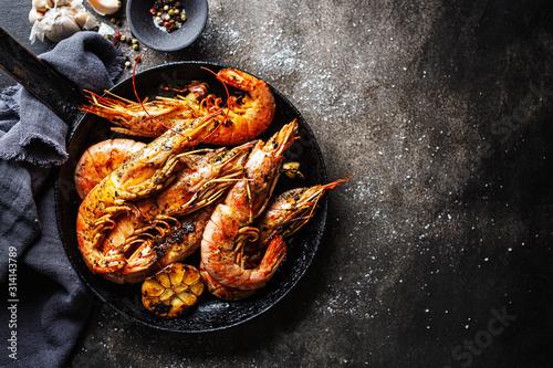 Cuadros en Lienzo Uncooked giant shrimps on dark table