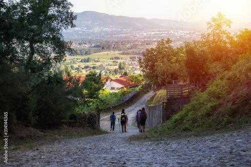 Fotografering A group of pilgrims walking the camino de santiago at sunset