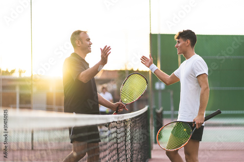 Photographie Father and Son Playing Tennis Outdoors.