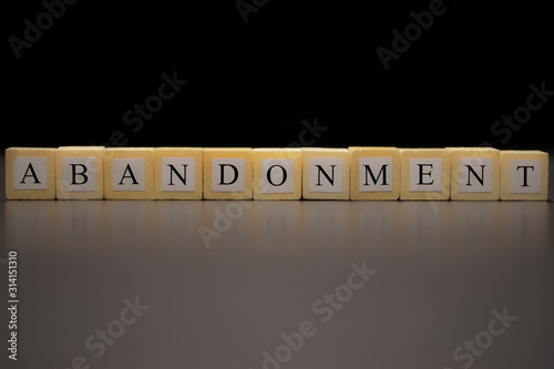 Photo ABANDONMENT written on wooden cubes  isolated on a black background