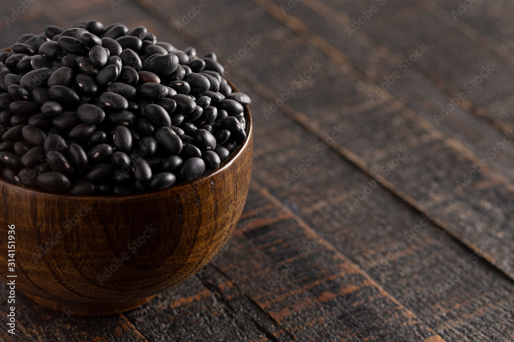Fototapeta Bowl of Dry Black Beans on a Rustic Wooden Table
