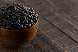 Fototapeta Kawa jest smaczna - Bowl of Dry Black Beans on a Rustic Wooden Table