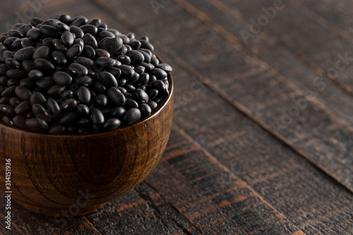 Fototapeta Bowl of Dry Black Beans on a Rustic Wooden Table obraz