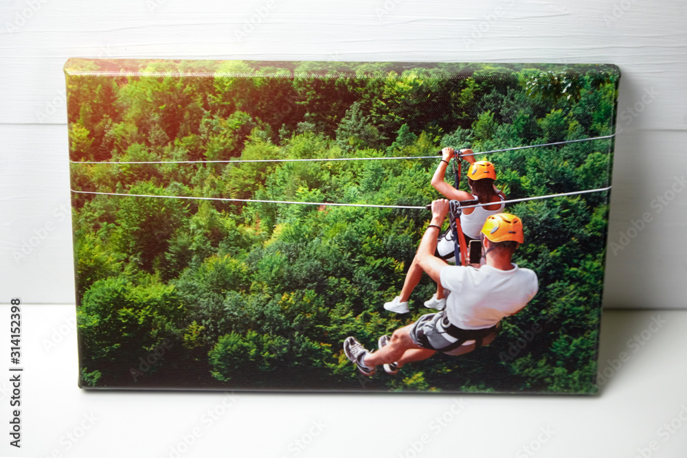 Obraz Canvas print on white table. Photo with gallery wrap method of canvas stretching on stretcher bar. Color photography with image of people on zip line. Interior decor fototapeta, plakat
