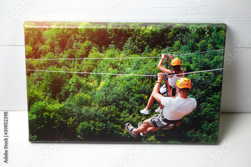 Obraz Canvas print on white table. Photo with gallery wrap method of canvas stretching on stretcher bar. Color photography with image of people on zip line. Interior decor - fototapety do salonu