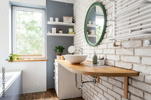 Bright interior of bathroom with window, wooden furniture and counter, round mirror and white brick wall Fototapet