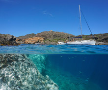 Mediterranean Sea In Summer, Rocky Coast With Boats And Some Fish Underwater, Split View Over And Under Water Surface, Spain, Costa Brava, Catalonia, Cap De Creus, Cala Jugadora