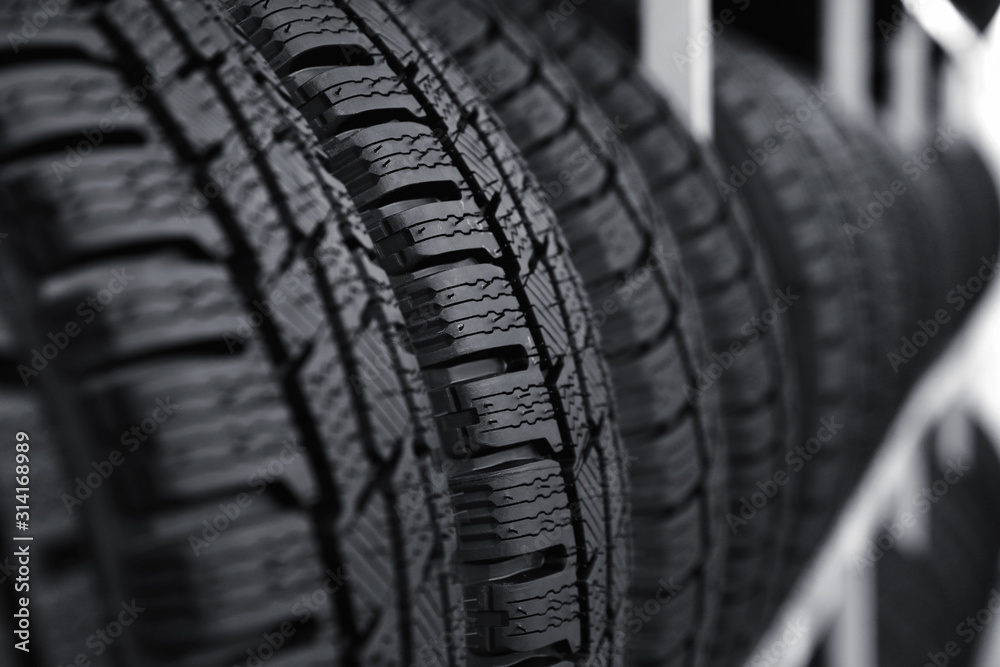 Fototapeta Car tires on rack in auto store, closeup