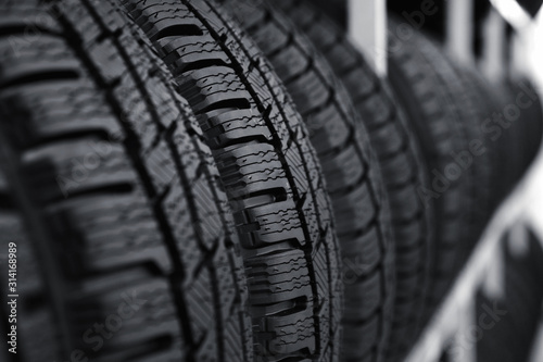 obraz PCV Car tires on rack in auto store, closeup