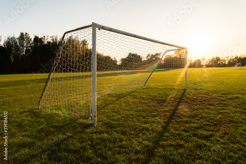 An empty soccer goal at sunset