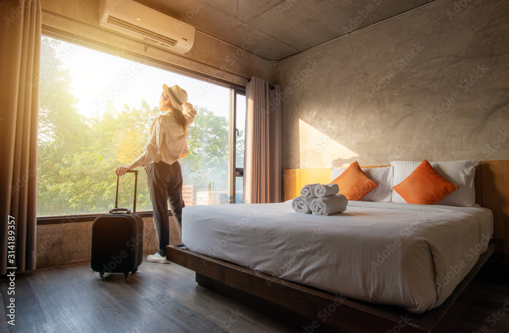 Fototapeta Portrait of tourist woman standing nearly window, looking to beautiful view with her luggage in hotel bedroom after check-in. Conceptual of travel and vacation.