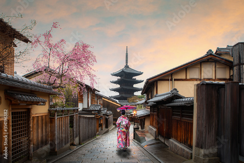 woman traveller wearing japanese traditional kimono with red umbrella sightseeing at famous destination Sannen Zaka Street with historical building house with cherry blossom in spring, Kyoto, Japan Fototapeta