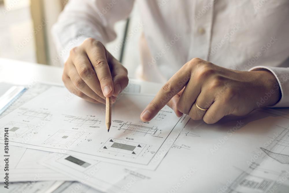 Fototapeta Engineering man showing blueprint detail for people buying house.