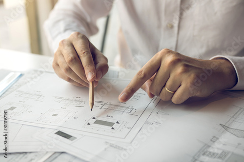 Fototapeta Engineering man showing blueprint detail for people buying house. obraz