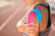 Sporty Woman With Physio Tape Applied On Shoulder At Stadium, Closeup