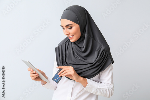 Photo Beautiful Arab woman with tablet computer and credit card on light background