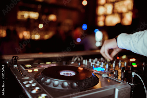 Fotografie, Obraz DJ plays live set and mixing music on turntable console at stage in the night club