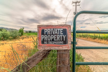No Trespassing Sign At A Private Property With Old Wire Fence And Metal Gate