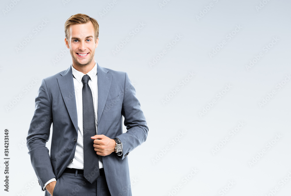 Fototapeta Portrait of happy smiling young businessman in confident suit, on grey background. Business success concept.