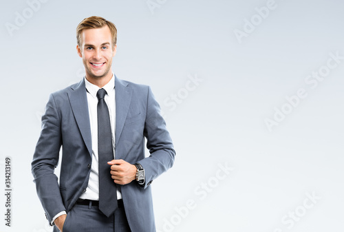 Fototapeta Portrait of happy smiling young businessman in confident suit, on grey background. Business success concept. obraz