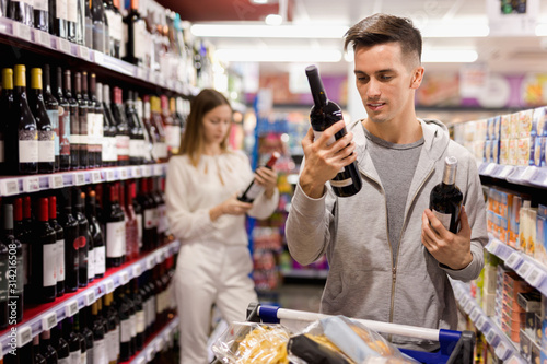 Portrait of young positive male customer selecting wine in supermarket